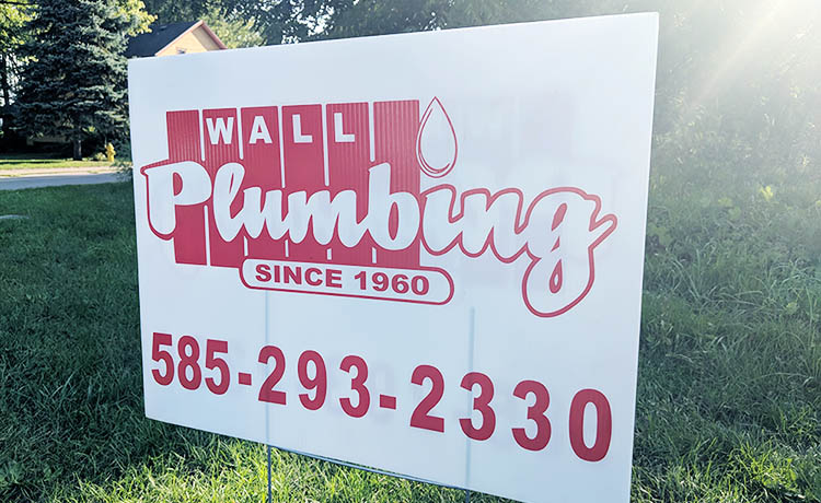 We're a family-owned company in Rochester NY. Wall Plumbing sign depicting our phone number and logo.